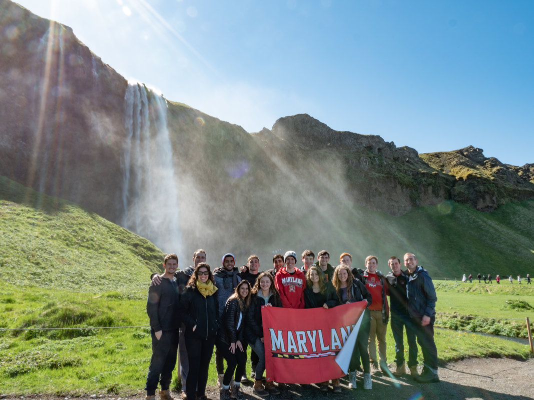 UMD students with instructor Mike Galczynski in Iceland in front of a waterfall
